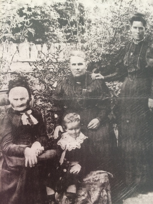 Taken not long before her death. Hannah Ann seated with daughter, Emily Warne, granddaughter, Emily Alice Waddell, and great grandson Snowy Norman.